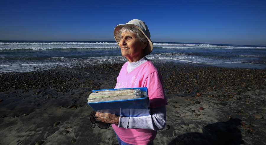 Tensia Moriel Trejo of Del Mar holds a scrapbook of Penguin Plunge events. She's missed just one of the New Year's Day swim events at Del Mar Beach in the past 30 years. — Nelvin C. Cepeda